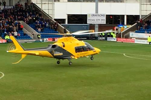 Un helicóptero aterriza en medio de un partido de fútbol para atender a un hincha