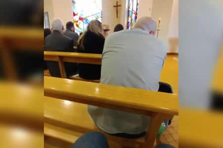 Un hombre mira fútbol durante una misa de la manera más ingeniosa