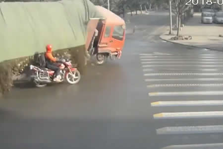 Un motociclista se libra por poco de morir sepultado por la carga de un camión