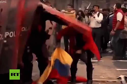 Un policía de Ecuador golpea a una mujer que intentaba recoger la bandera nacional del piso