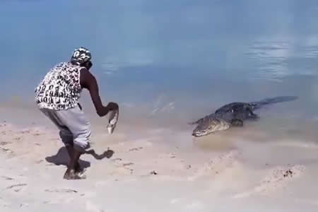 Un indígena australiano juega con su 'mascota', un enorme cocodrilo