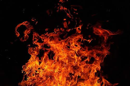 Un hombre sigue pescando con toda calma mientras un incendio avanza a su espalda