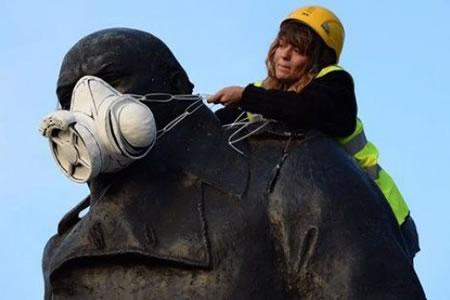 Unas 200 personas cubren con máscaras estatuas en Bruselas por un aire limpio