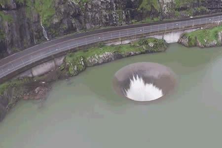 Un desagüe de presa a vista de dron se asemeja a un agujero negro