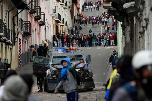 Un tanqueta policial a gran velocidad dispersa una manifestación en el Centro Histórico de Quito
