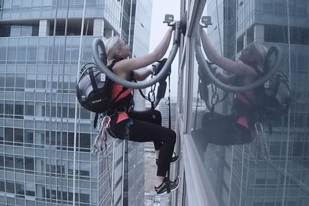 Una joven escala un rascacielos con la ayuda... ¡de una aspiradora!